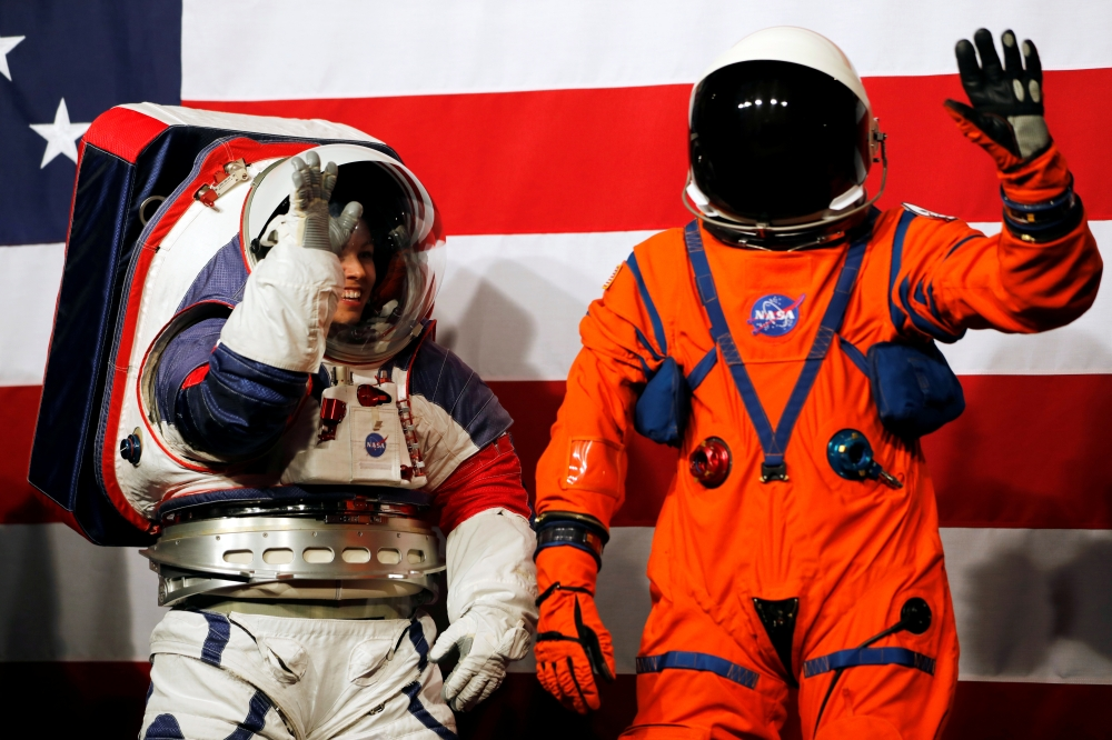 Advanced Space Suit Engineer at NASA Kristine Davis, left, wears the xEMU prototype space suit next to lead engineer Dustin Gohmert wearing the Orion crew survival spacesuit prototype for the next astronaut to the moon by 2024, during its presentation at NASA headquarters in Washington, on Tuesday. — Reuters