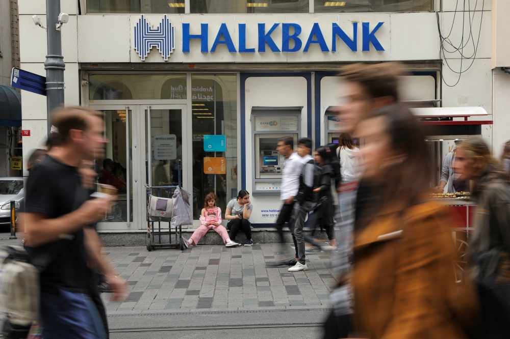 People walk past by a branch of Halkbank in central Istanbul, Turkey, on Wednesday. The case against its second biggest state lender Halkbank was a reminder that Turkey's economy could be vulnerable to measures that hit its financial system. – Reuters