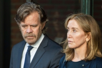 Actress Felicity Huffman, escorted by her husband actor William H. Macy, exits the John Joseph Moakley United States Courthouse in Boston, where she was sentenced by Judge Talwani for her role in the College Admissions scandal, in this Sept. 13, 2019 file photo. — AFP