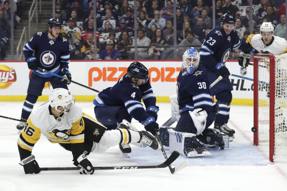 Pittsburgh Penguins center Zach Aston-Reese (46) scores on Winnipeg Jets goaltender Laurent Brossoit (30) in the first period at Bell MTS Place in Winnipeg, Manitoba, Canada, in this Oct. 13, 2019 file photo. — Reuters