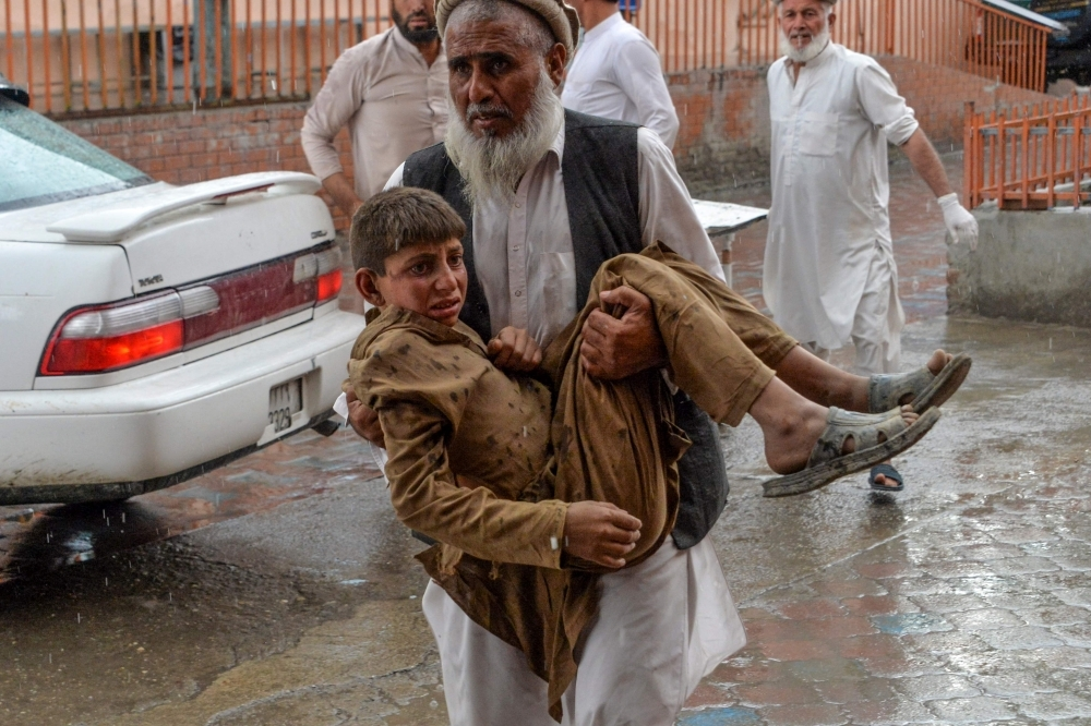 A volunteer carries an injured youth to hospital, following a bomb blast in Haska Mina district of Nangarhar Province, Afghanistan, on Friday. — AFP