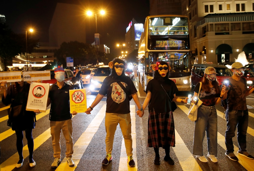 People wearing masks gather during an anti-government protest in Hong Kong, China, on Friday. — Reuters