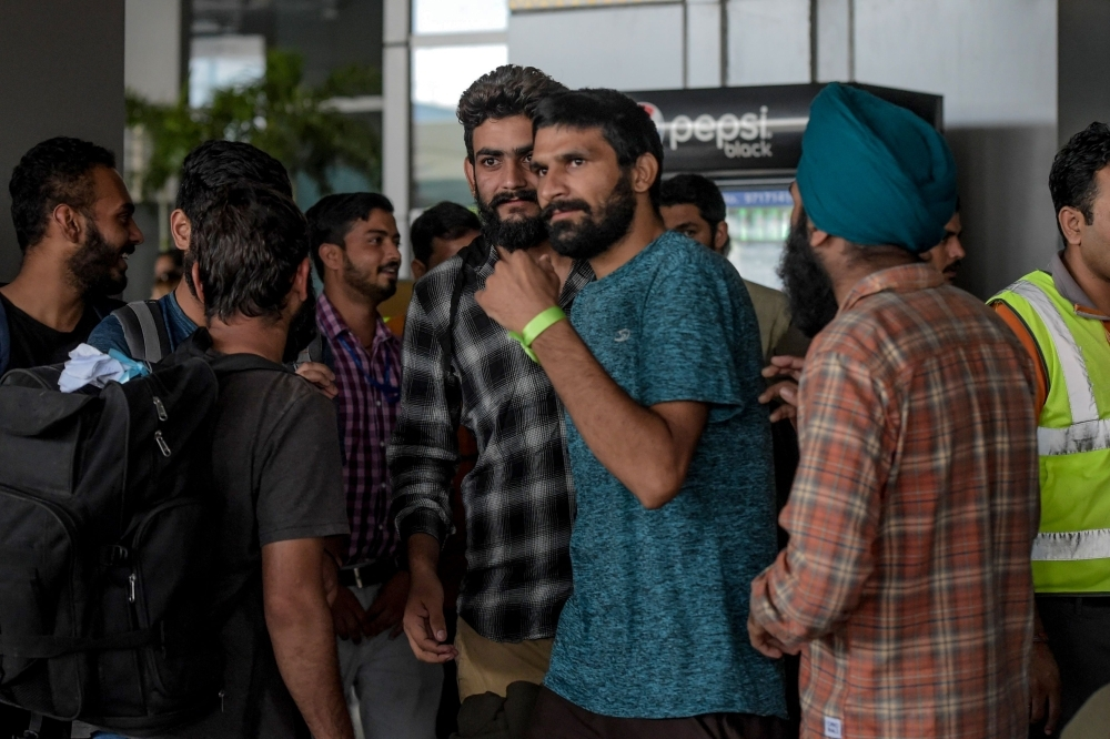 Indian nationals arrive at Indira Gandhi International airport in New Delhi on Friday, after being deported from Mexico as they tried to enter the United States. — AFP