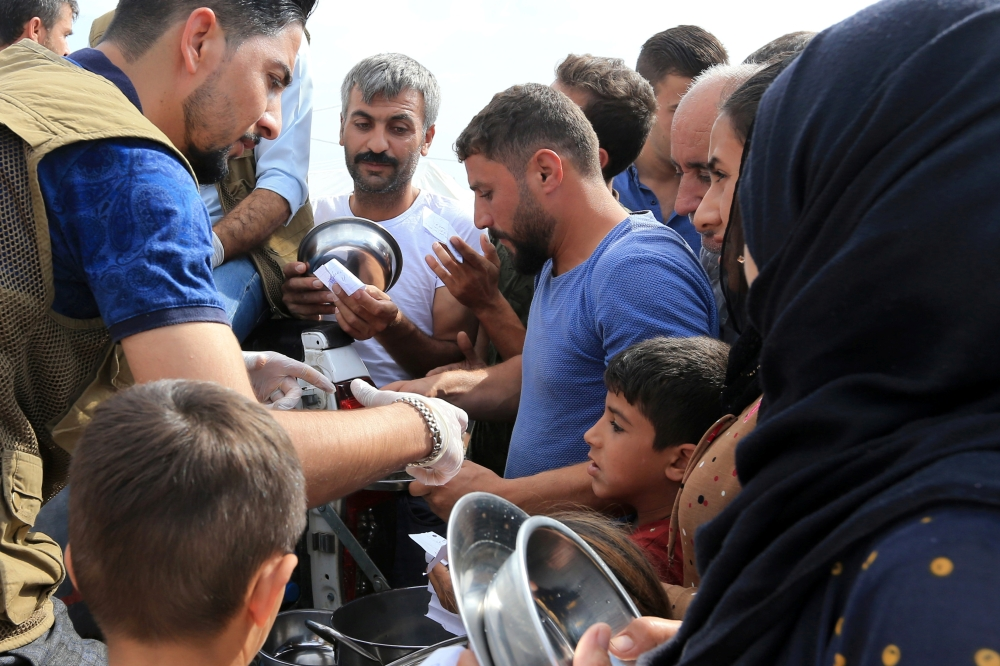 Syrian displaced families, who fled violence after the Turkish offensive in Syria, gather to get food from Barzani charity at a refugee camp in Bardarash on the outskirts of Dohuk, Iraq, on Friday. — Reuters