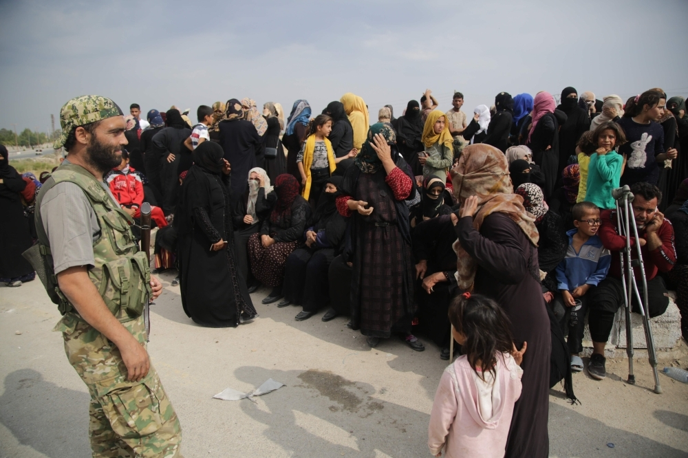 A member of the Turkey-backd forces looks at displaced Syrians waiting to receive aid provided by the Turkish Red Crescent, in the Syrian border town of Tal Abyad which was seized last week. Turkish and Kurdish leaders traded accusations of violating a US-brokered truce in northeastern Syria, which aimed to halt a Turkish-led offensive on Kurdish forces that has killed dozens of civilians and prompted hundreds of thousands to flee their homes, in the latest humanitarian crisis of Syria's eight-year civil war. — AFP