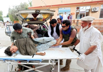 Men carry an injured person to a hospital after a bomb blast at a mosque in Jalalabad in Afghanistan, Friday. — Reuters