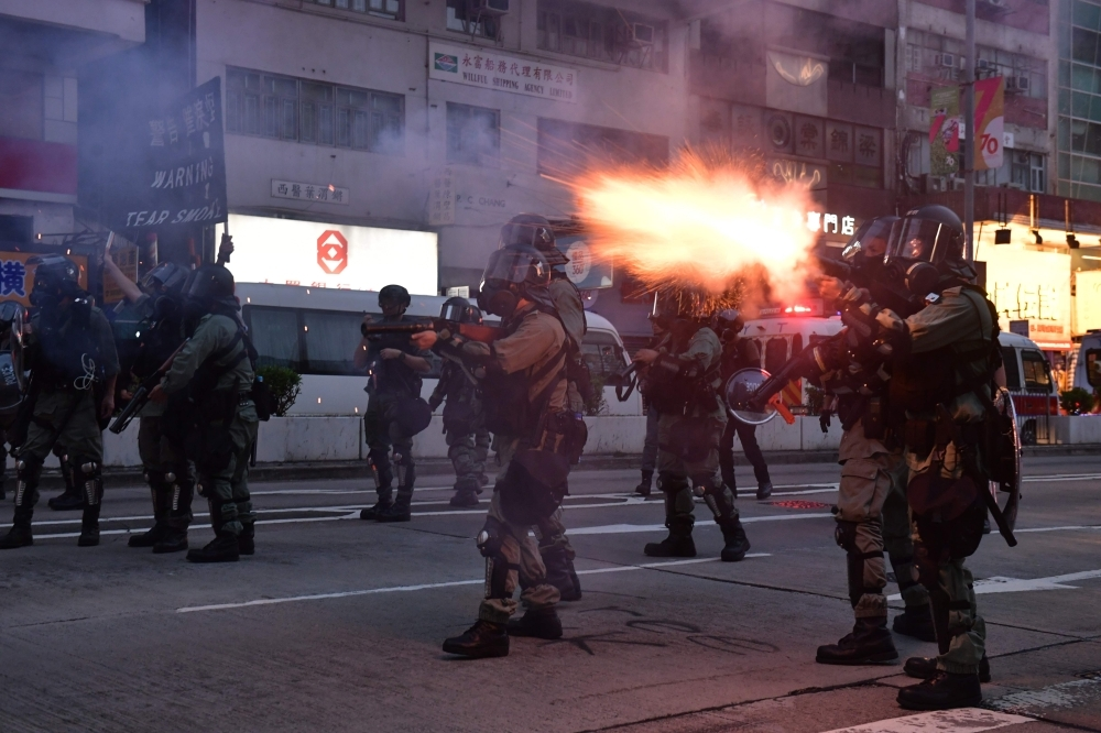 Riot police fire tear gas against protesters in Mongkok during a pro-democracy march in the Kowloon district in Hong Kong, Sunday. — AFP
