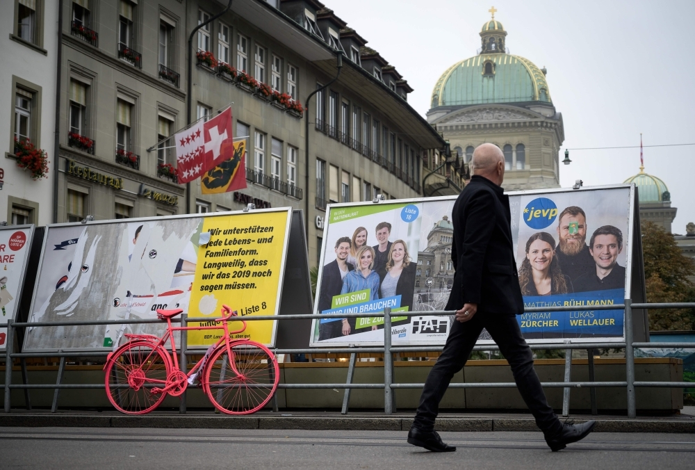 A man walks past electoral posters with the dome of the Swiss house of parliament in the background in Bern during Switerland's general election on Sunday. — AFP