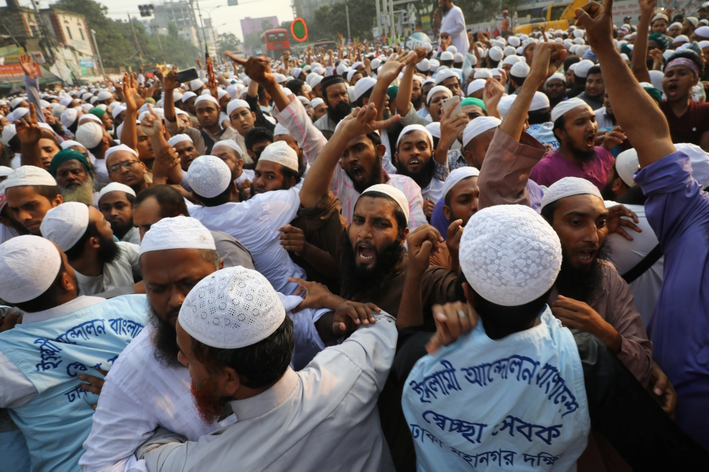 Activists shout slogans as they take part in a protest, a day after deadly clashes when police shot at Bangladeshi Muslims protesting allegedly blasphemous Facebook messages, in Bangladesh, on Monday. — Reuters