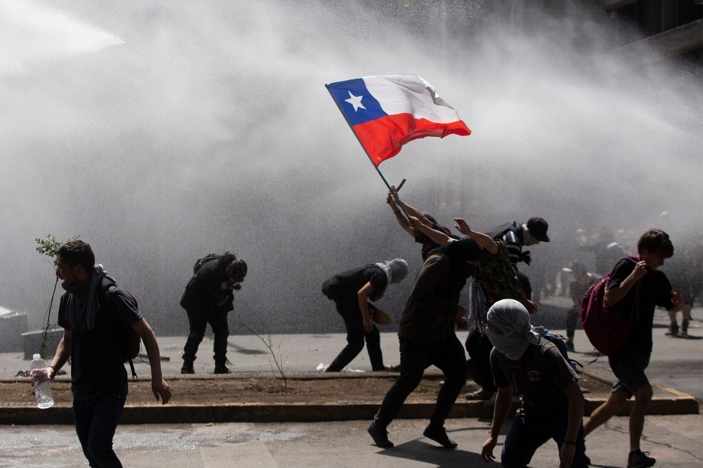 Demonstrators clash with riot police during a protest in Santiago, Chile, on Monday. — AFP