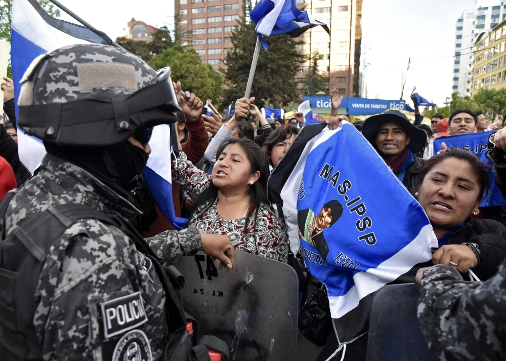 Supporters of Bolivia's president and candidate Evo Morales are being contained by security forces as they shout slogans against supporters of the candidate of the 'Comunidad Ciudadana' party, former president (2003-2005) Carlos Mesa, as both groups gather outside Supreme Electoral Tribunal in La Paz, on Monday. — AFP