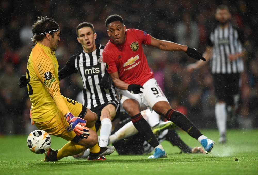 Manchester United's French striker Anthony Martial (C) shoots to score the second goal past FK Partizan's Serbian goalkeeper Vladimir Stojkovic (L) during the UEFA Europa League Group L football match between Manchester United and Partizan Belgrade at Old Trafford in Manchester, north west England, on Thursday. — AFP