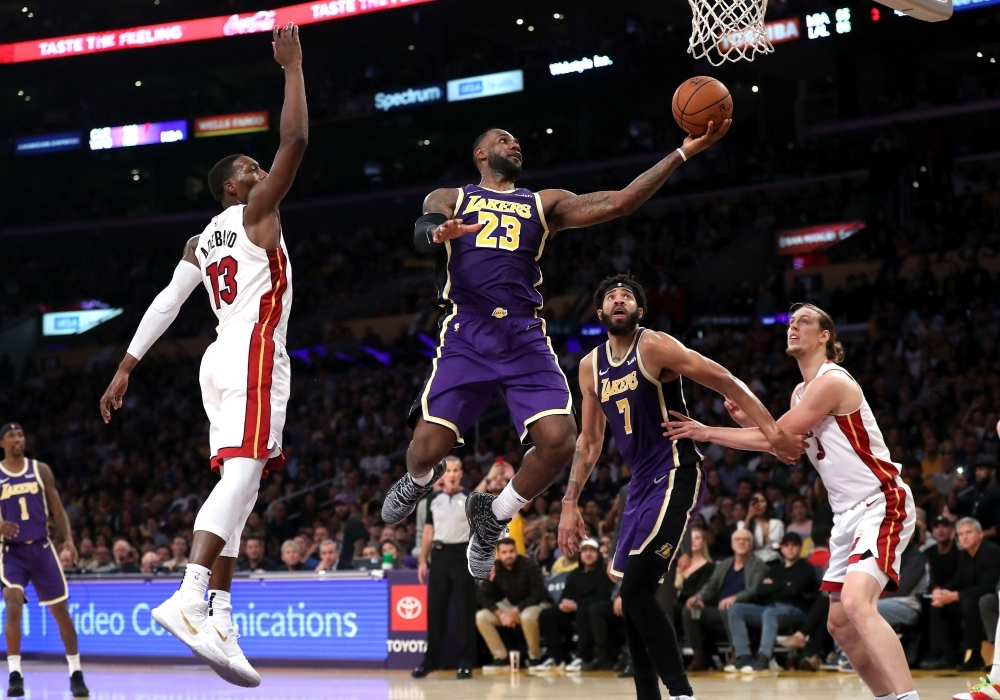 LeBron James (23) of the Los Angeles Lakers drives past Bam Adebayo (13) of the Miami Heat for a layup during the second half of a game at Staples Center on in Los Angeles, California on Friday.  — AFP