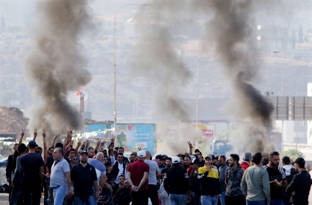 Lebanese protesters gather next to burning tires to block the southern entrance of the capital of north Lebanon Tripoli, as anti-government demonstrations continued on Tuesday across the country. -AFP