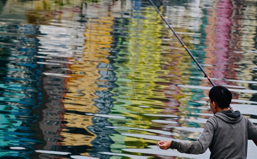 A man fishing at the Zhangbin Fishing Port as the water reflects the color painted houses in Keelung, northern Taiwan. — AFP