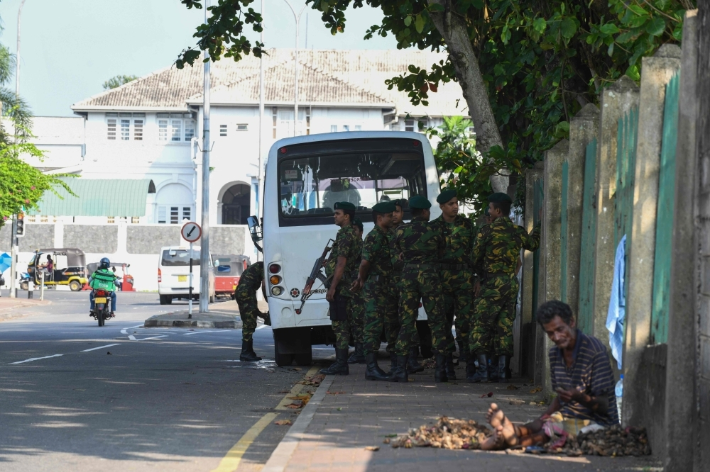 Special Task Force (STF) soldiers stand guard near the Welikada prison in Colombo on Tuesday, as inmates protest the pardon for a man who murdered a Swedish teenager in 2005. — AFP