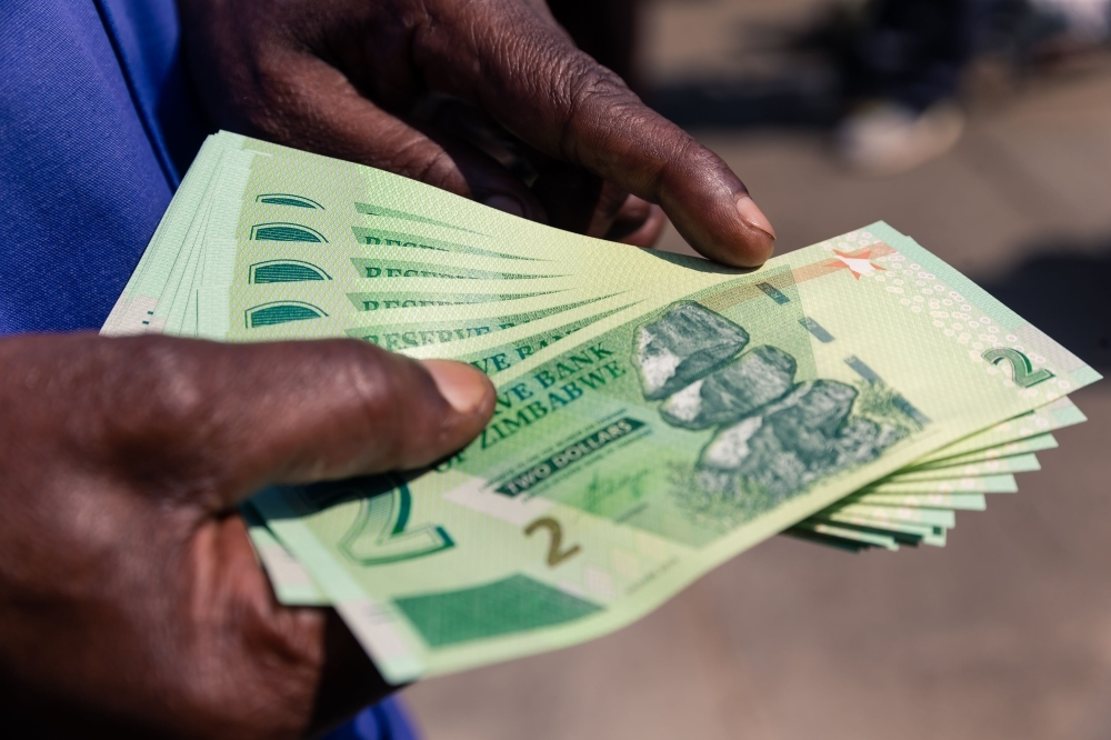 A man shows a wad of the new Zimbabwe two-dollar notes he received from a bank in Harare on Tuesday. — AFP