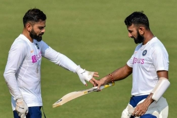 India's captain Virat Kohli (L) inspects teammate Cheteshwar Pujara's bat during a training session ahead of the first test match between India and Bangladesh at Holkar Cricket Stadium in Indore on Monday. — AFP