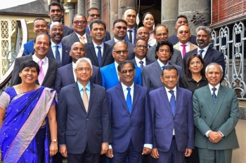 Mauritius' re-elected Prime Minister Pravind Jugnauth, front, second left, poses with President Barlen Vyapoory, front, center, and his Cabinet after his swearing-in ceremony at the state house in Reduit on Tuesday. — AFP