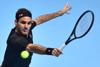 Switzerland's Roger Federer returns against Italy's Matteo Berrettini during their men's singles round-robin match on day three of the ATP World Tour Finals tennis tournament at the O2 Arena in London on Tuesday. Federer won the match 7-6, 6-3. — AFP