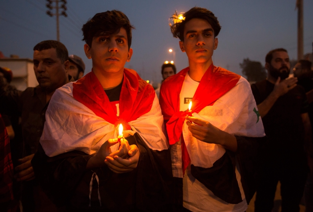 Iraqis march with lit candles during a symbolic funeral in honor of protesters killed during anti-government demonstrations in the southern city of Basra on Tuesday. -AFP