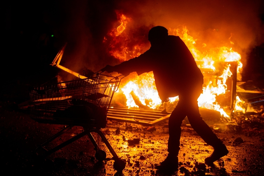 Demonstrators clash with security forces during a protest against the government of Sebastian Pinera in Santiago on Tuesday. -AFP