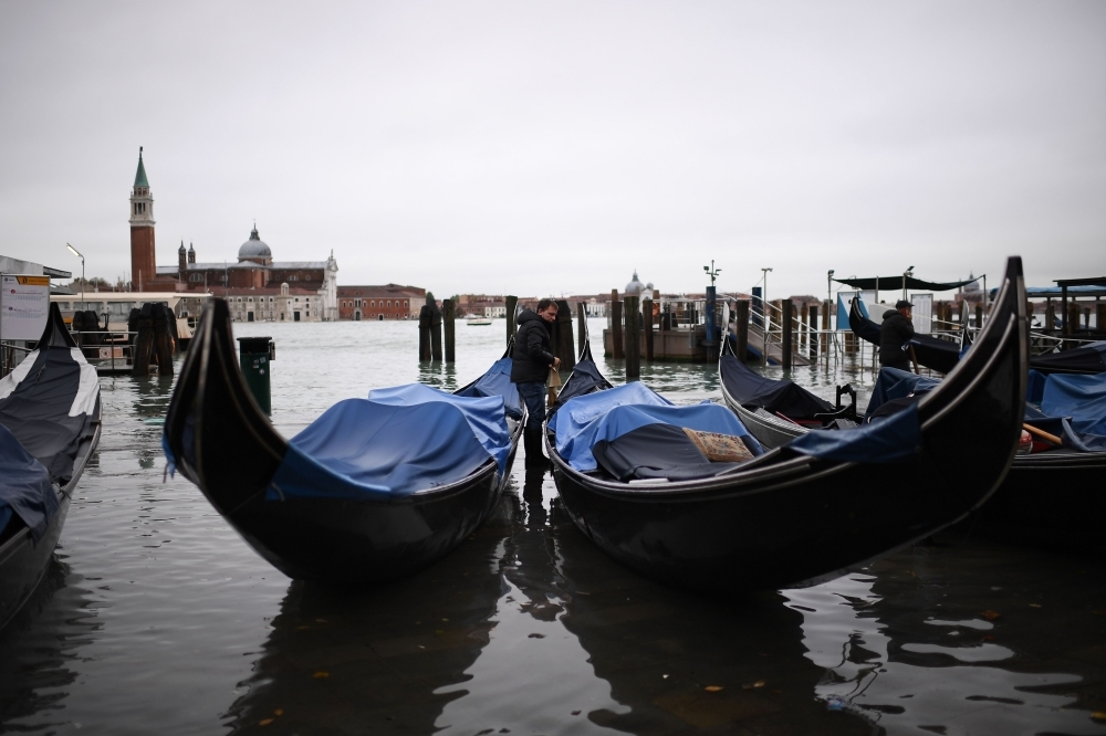 Stranded gondolas are pictured at the Riva degli Schiavoni embankment, with the basilica of San Giorgio Maggiore in background, after an exceptional overnight