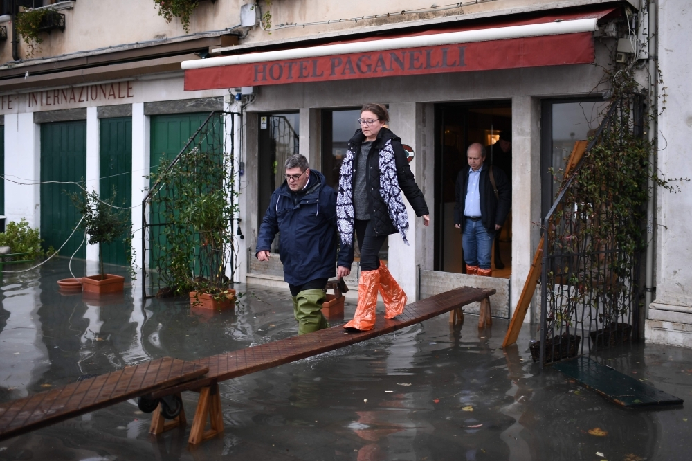 People use a makeshift footbridge to exit a flooded hotel after an exceptional overnight