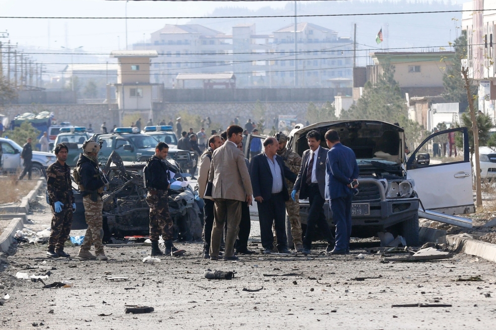 Security personnel and investigators gather at the site of a suicide attack in Kabul on Wednesday. -AFP