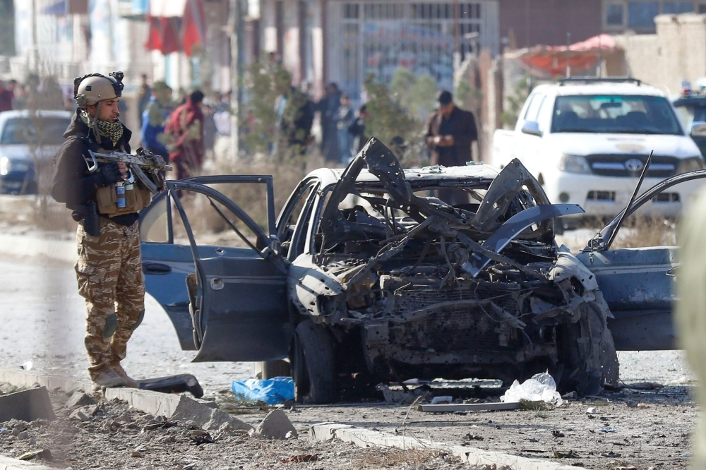 Security personnel and investigators gather at the site of a suicide attack in Kabul on Wednesday. — AFP