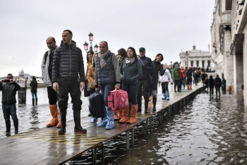 Pedestrians walk on a footbridge across the flooded Riva degli Schiavoni embankment after an exceptional overnight