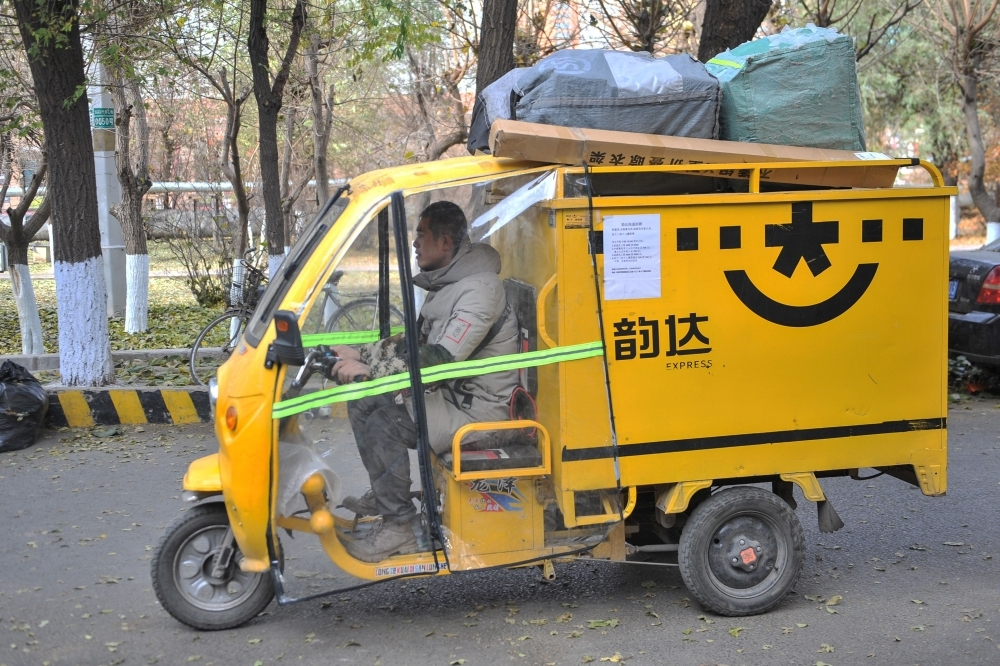 A worker drives a tricycle to deliver packages to customers in Shenyang in China's northeastern Liaoning province on Thursday. — AFP
