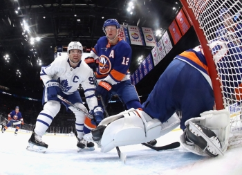 John Tavares No. 91 of the Toronto Maple Leafs and Josh Bailey No. 12 of the New York Islanders battle for position during the second period at NYCB Live's Nassau Coliseum on Wednesday in Uniondale, New York. The Islanders defeated the Maple Leafs 5-4. — AFP