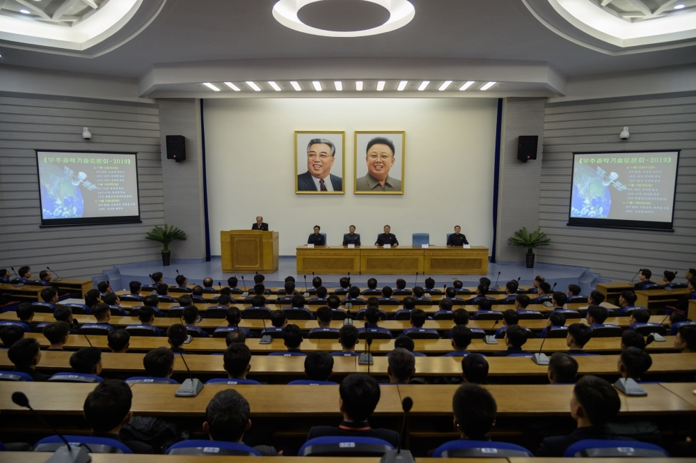 In a photo taken on Nov. 12, 2019 North Korean scientists sit before the portraits of late North Korean leaders Kim Il Sung and Kim Jong Il as they attend a symposium on 'Space Science and Technology 2019' at the Sci-tech Complex in Pyongyang. — AFP