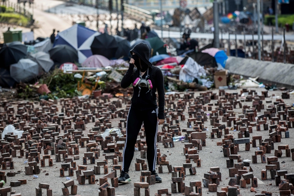 A protester (C) stands amongst bricks placed on a barricaded street outside The Hong Kong Polytechnic University in Hong Kong on Friday. Pro-democracy protesters challenging China's rule of Hong Kong on Thursday choked the city for a fourth straight working day, firing arrows at police, barricading roads and disrupting transport links, as schools and businesses closed. — AFP