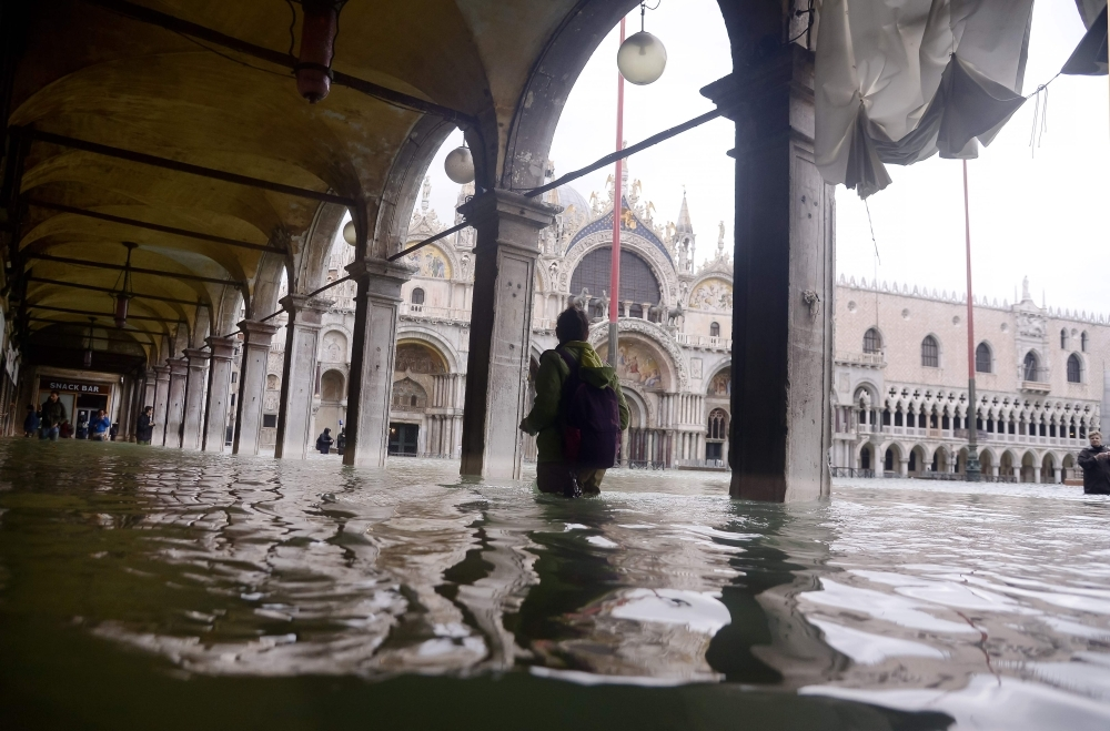 A person walks across a flooded arcade by St. Mark's Basilica on Friday in Venice, two days after the city suffered its highest tide in 50 years. Flood-hit Venice was bracing for another exceptional high tide as Italy declared a state of emergency for the UNESCO city where perilous deluges have caused millions of euros worth of damage. — AFP