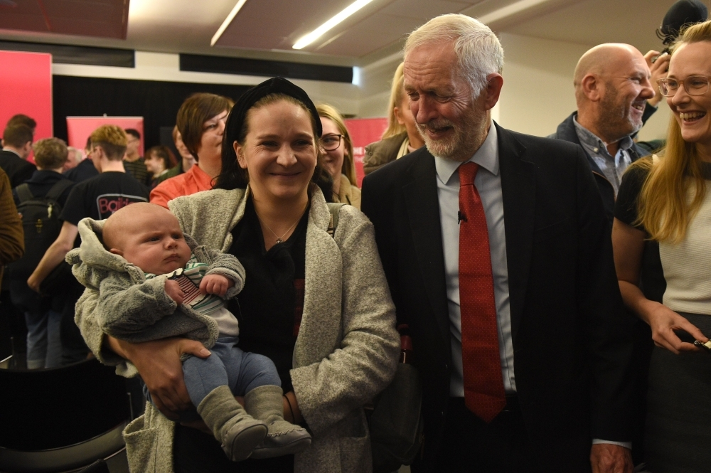 Opposition Labour party leader Jeremy Corbyn meets a supporter and baby after giving a speech on digital infrastructure policy at an election campaign event in Lancaster, northwest England, on Friday. — AFP