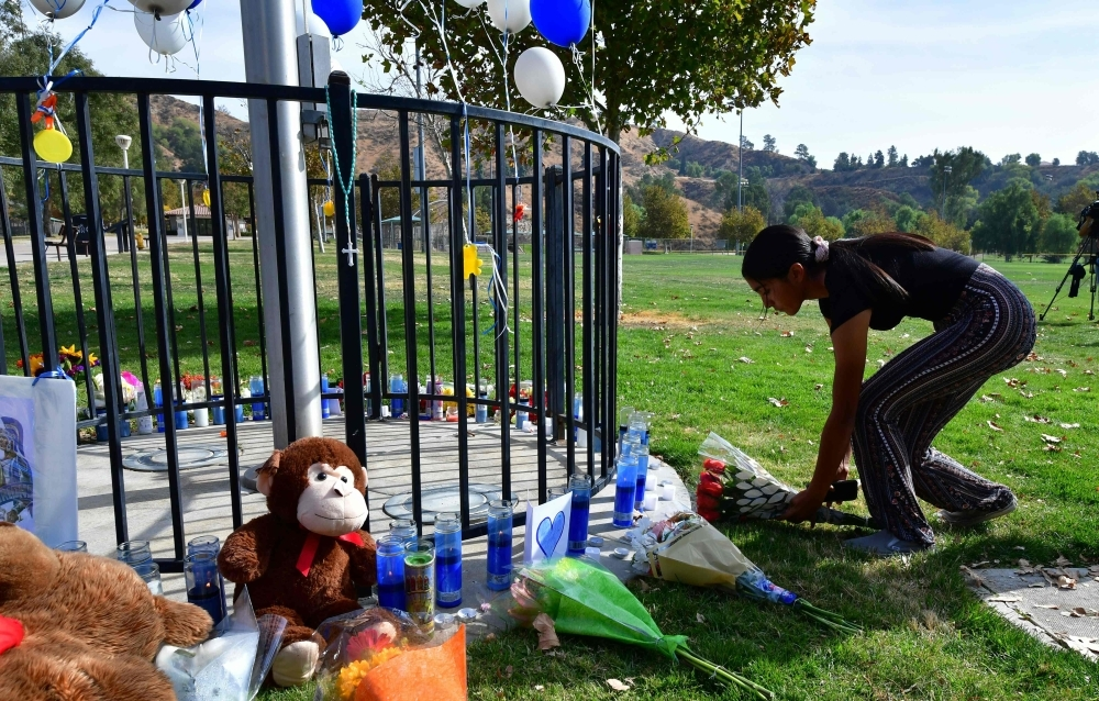 Flowers are placed at a makeshift memorial at Central Park on Friday in Santa Clarita, California, not far from Saugus High School, where parents and children were reunited following the school shooting a day earlier. — AFP