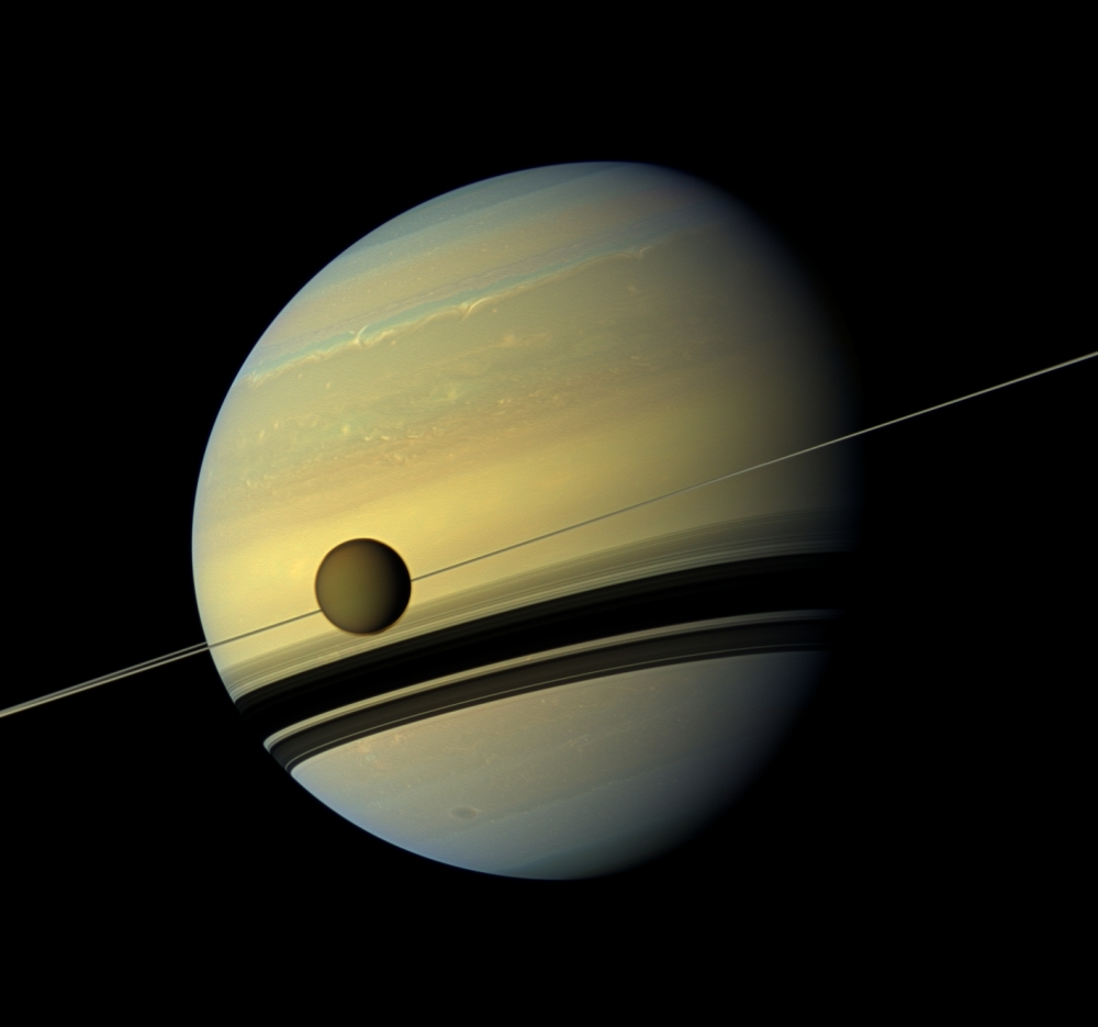 This file photo taken on Aug. 31, 2012 shows a giant of a moon appearing before a giant of a planet undergoing seasonal changes in this natural color view of Titan and Saturn from NASA's Cassini spacecraft.  — AFP