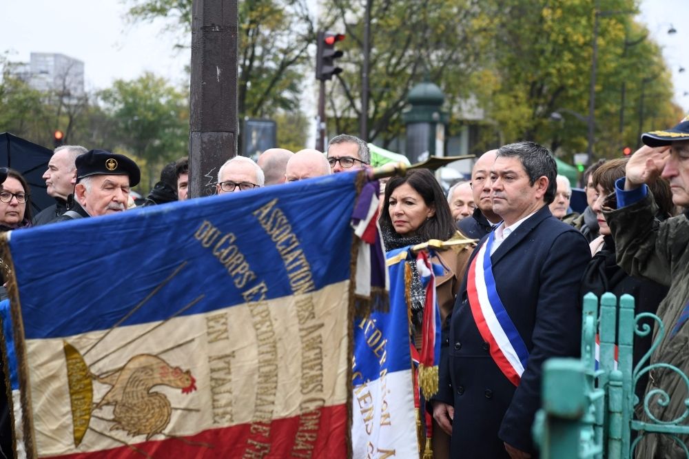 Paris' mayor Anne Hidalgo (C) and mayor of Paris' 13th district Jerome Coumet (2ndR) spend a moment in silence, on Monday at Place d'Italie in Paris in front of the  the damaged monument to World War II hero Marshal Alphonse Juin which was defaced by demonstrators dressed in black two days ago during the