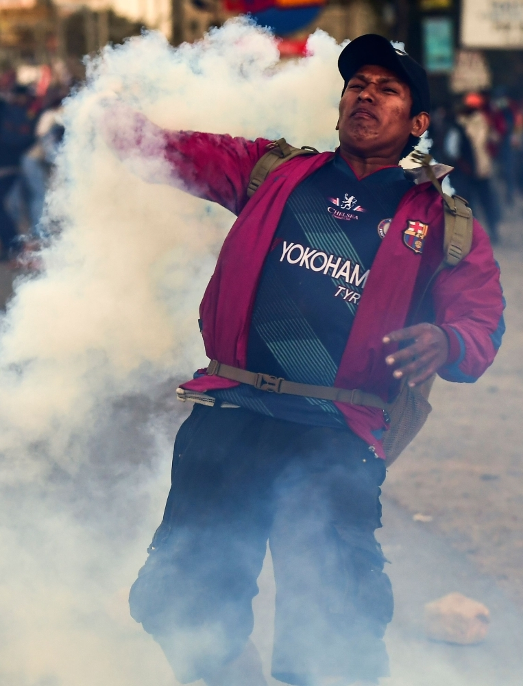 A supporter of Bolivian ex-president Evo Morales, returns tear gas to riot police while block a road in the outskirts of Sacaba, Chapare province, Cochabamba, on Monday. -AFP