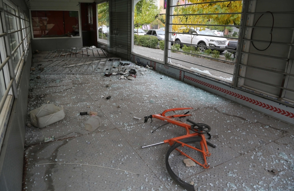 Shattered glass lies on the ground with a bicycle in Tehran on Tuesday. -AFP