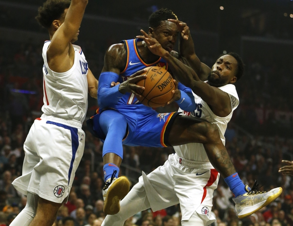 Jerome Robinson (1) and Patrick Beverley (21) of the Los Angeles Clippers defend Dennis Schroder (17) of the Oklahoma City Thunder as he goes up for a basket during the first half of a game at Staples Center in Los Angeles, California on Monday. — AFP