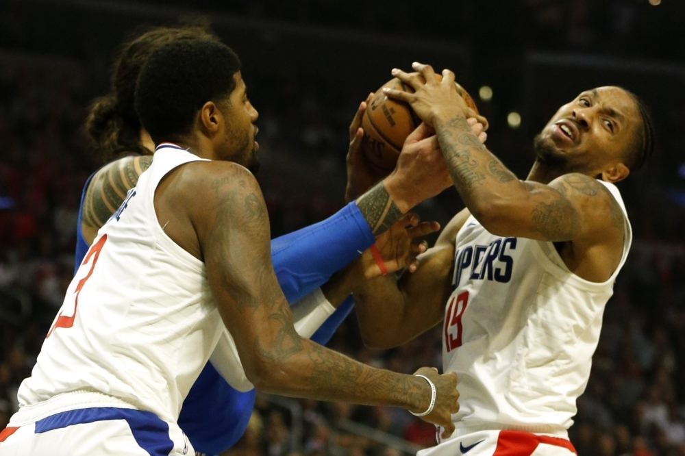 Paul George (13), Rodney McGruder (19), both of the Los Angeles Clippers, and Steven Adams (12) of the Oklahoma City Thunder fight for control of the ball during the second half at Staples Center in Los Angeles, California on Monday. — AFP