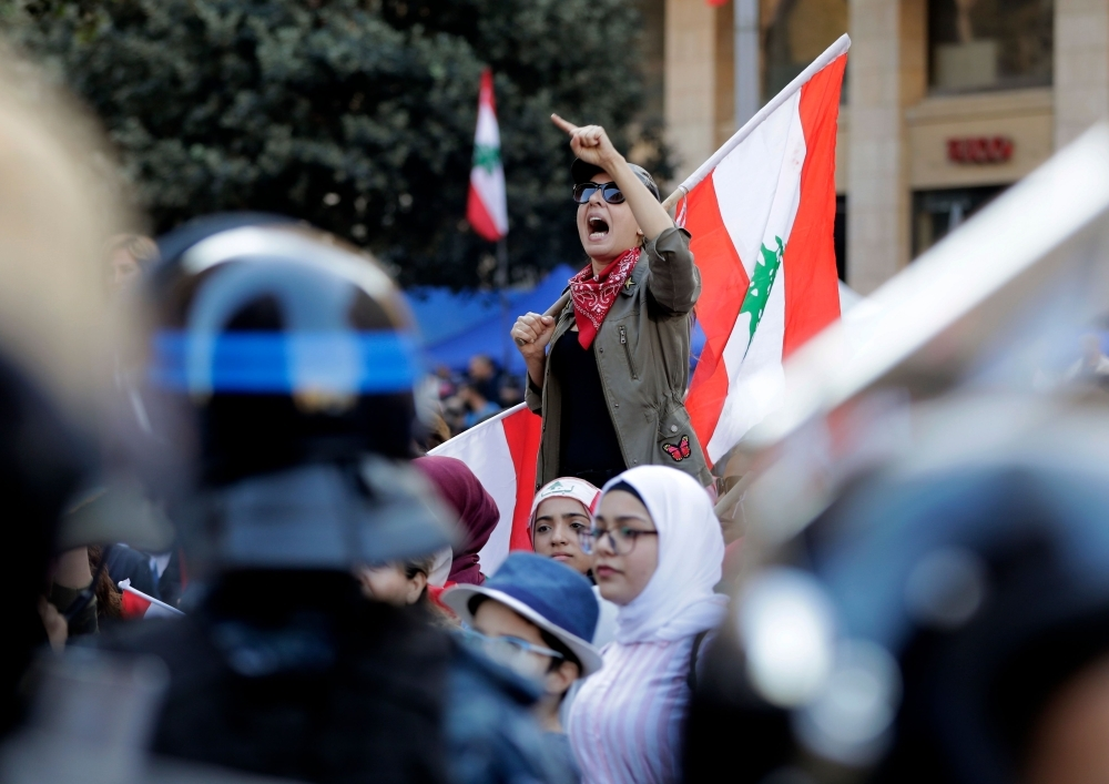 A Lebanese protester holds a national flag as she chants slogans during a demonstration at Riad Al-Solh square near the government palace and the parliament headquarters in the capital Beirut's downtown district on Tuesday. — AFP