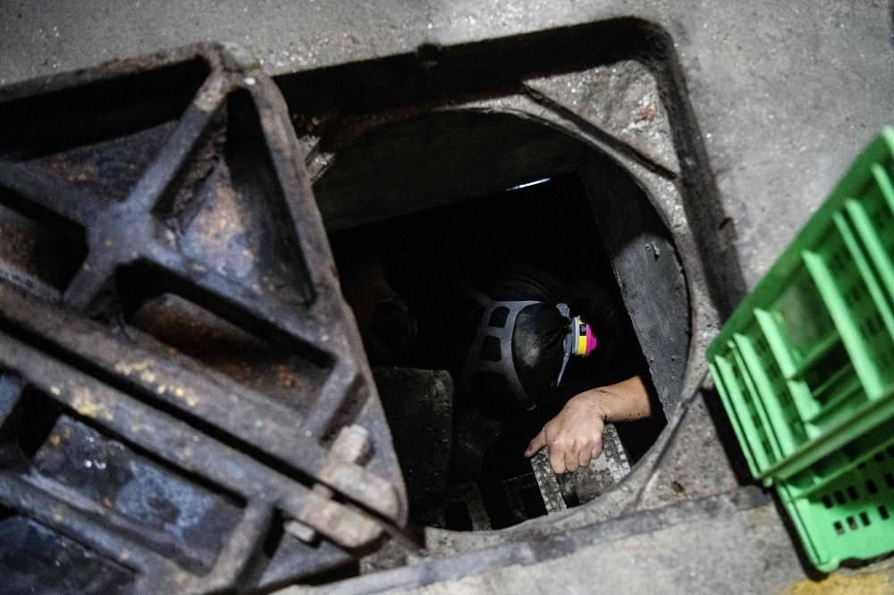 A protester climbs down into a sewer entrance as he and others try to find an escape route from the Hong Kong Polytechnic University in the Hung Hom district of Hong Kong early morning on Tuesday. — AFP