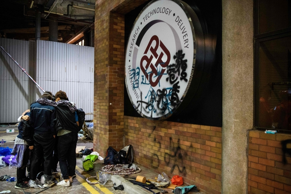 A group of protesters huddle together after deciding not to climb down into a sewer entrance while trying to find an escape route from the Hong Kong Polytechnic University in the Hung Hom district of Hong Kong early morning on Tuesday. — AFP
