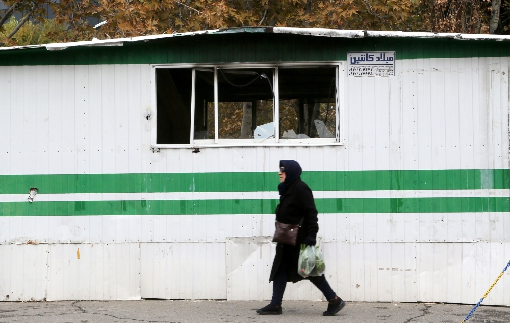 An Iranian woman walks past a police station that was set ablaze by protesters in Tehran on Tuesday. — AFP