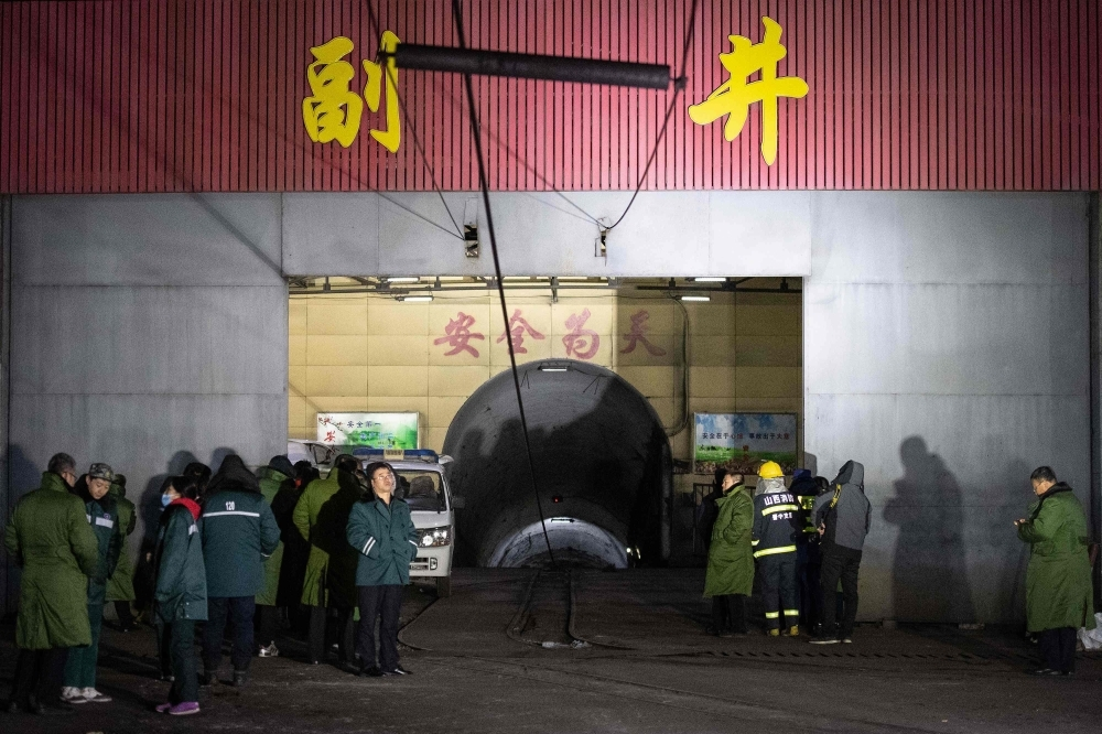 Rescuers and staff members wait outside the site of a coal mine explosion in Pingyao, in China's northern Shanxi province, early on Tuesday. — AFP