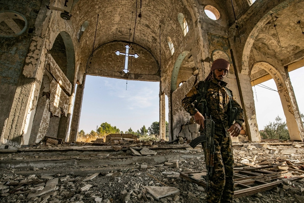 A member of the Khabour Guards (MNK) Assyrian Syrian militia, affiliated with the Syrian Democratic Forces (SDF), walks in the ruins of the Assyrian Church of the Virgin Mary, which was previously destroyed by Daesh (the so-called IS) fighters, in the village of Tal Nasri south of the town of Tal Tamr in Syria's northeastern Hasakah province in this Nov. 15, 2019 file photo. — AFP